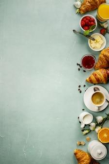 Kontinentales frühstück auf grünem tischhintergrund, draufsicht