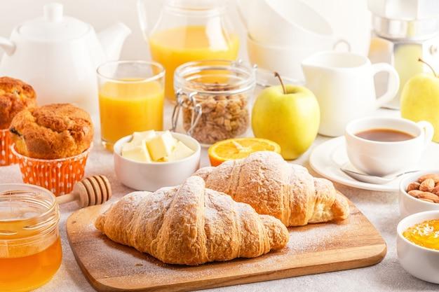 Kontinentales frühstück mit frischen croissants, orangensaft und kaffee, selektiver fokus.