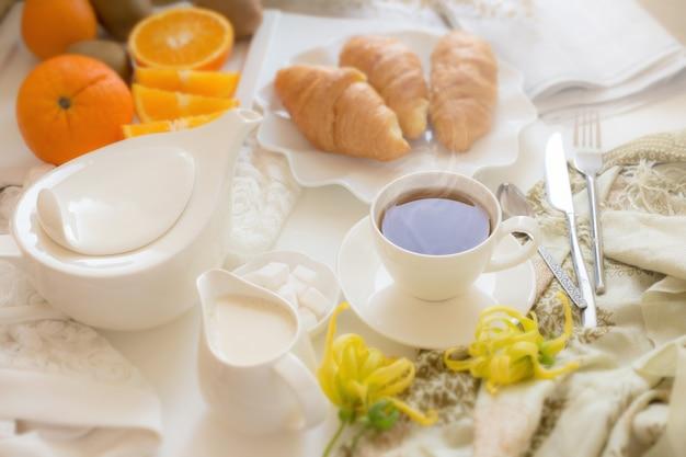 Kontinentales frühstück mit goldenen französischen hörnchenfrüchten und tasse tee