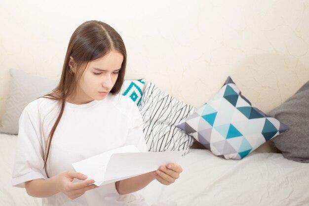 Konto, hinweis. ein mädchen liest zu hause einen zahlungsbeleg, einen brief, schaut sich den text genau an
