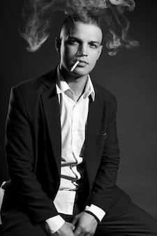 Kontrastieren sie porträt eines rauchenden manngeschäftsmannes in einem teuren anzug auf dunkelheit