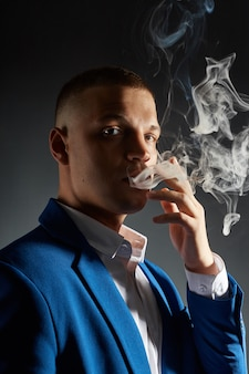 Kontrastieren sie porträt eines rauchenden manngeschäftsmannes in einem teuren anzug auf dunklem hintergrund.