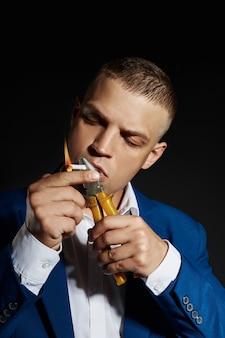 Kontrastieren sie porträt eines rauchenden manngeschäftsmannes in einem teuren anzug auf einem dunklen hintergrund. erfolgreicher emotionaler managergeschäftsmann, der gestenhände und rauchende zigarette auf einem schwarzen aufwirft