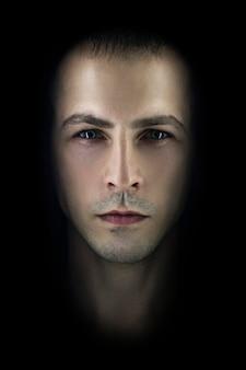 Kontrastierender männlicher porträtschwarzhintergrund. licht