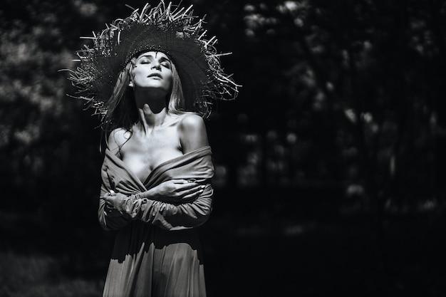 Kontrastierendes schwarz-weiß-porträt eines sexy glamourösen mädchens in hut und kleid in der natur. mit filmkorn, rauschen