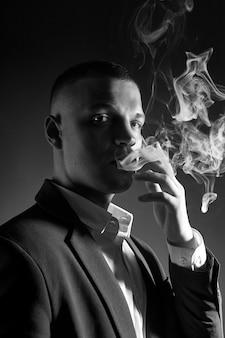 Kontrastporträt eines rauchenden manngeschäftsmannes in einem teuren anzug