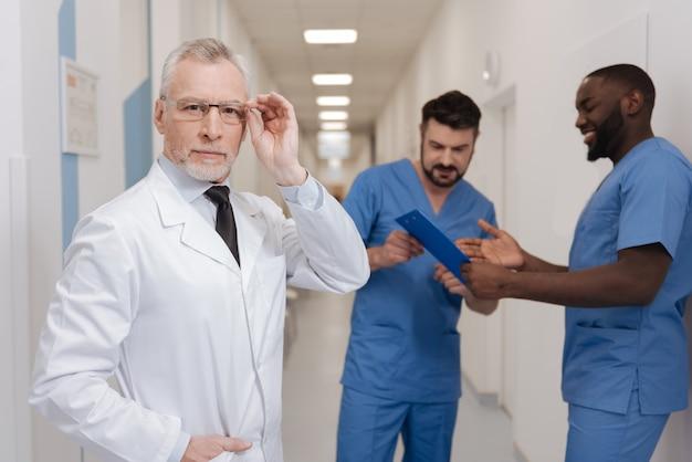 Kontrolle des prüfungsprozesses von praktikanten. selbstbewusster kluger bärtiger sanitäter, der in der klinik arbeitet und brillen berührt, während praktikanten im hintergrund gespräche führen