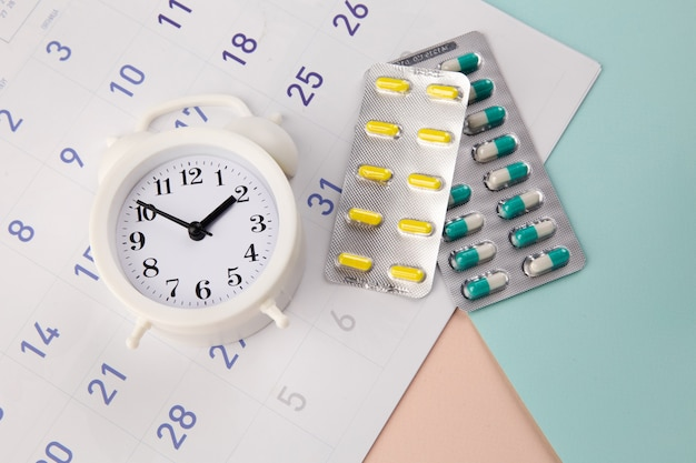 Kontrollieren sie die zeit, um pillen einzunehmen. uhr mit pillen auf einem monatskalender.