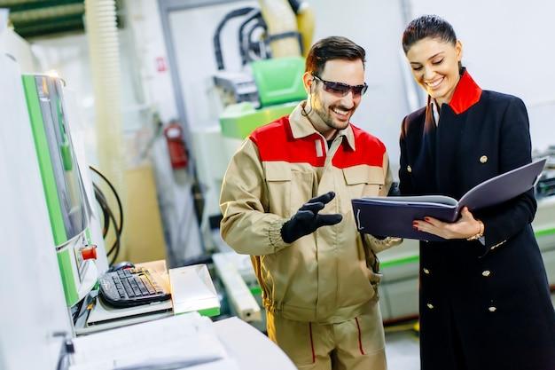 Kontrollprozess der jungen frau in der fabrik mit männlicher arbeitskraft