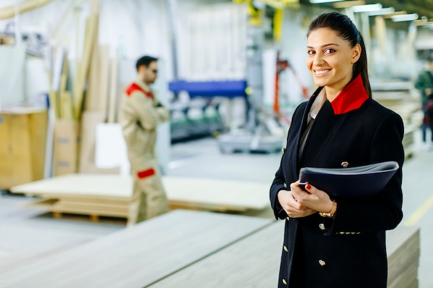Kontrollprozess der recht jungen frau in der fabrik