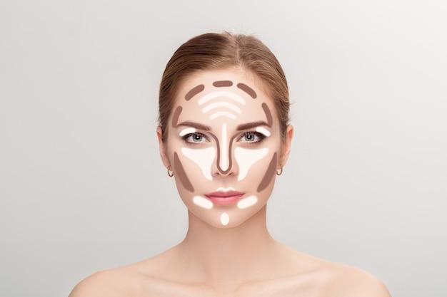 Konturierung. bilden sie frauengesicht auf grauem hintergrund. make-up konturieren und hervorheben. professionelle gesichts-make-up-probe