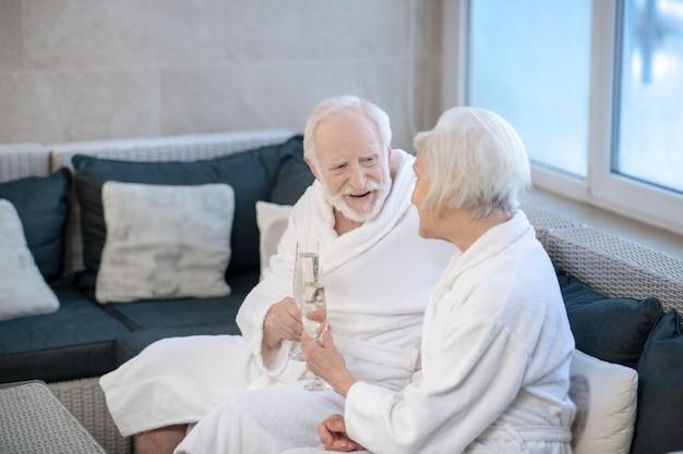 Konversation. reifes paar in weißen gewändern, das auf dem sofa sitzt und etwas bespricht