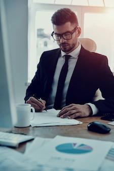 Konzentration auf die arbeit. ernster junger mann in formeller kleidung, der die formulare ausfüllt, während er im büro sitzt