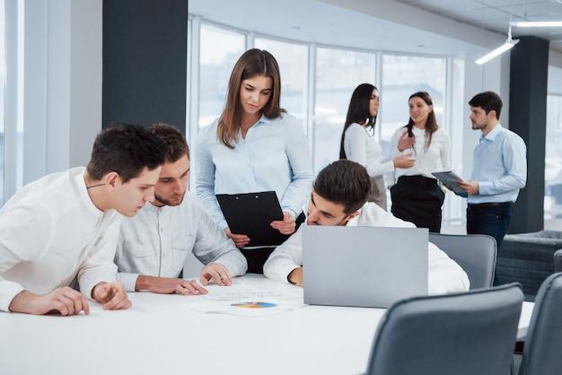 Konzentration auf die geschäftsplanung. eine gruppe junger freiberufler im büro unterhält sich und arbeitet mit dokumenten