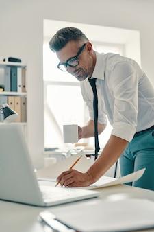 Konzentration bei der arbeit. hübscher junger mann in hemd und krawatte, der etwas schreibt und lächelt, während er im büro steht