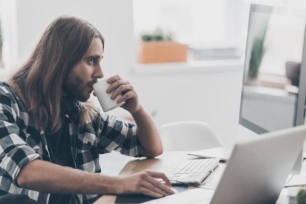 Konzentration bei der arbeit. schöner junger mann mit langen haaren, der am computer arbeitet und kaffee trinkt, während er an seinem schreibtisch im kreativbüro sitzt sitting