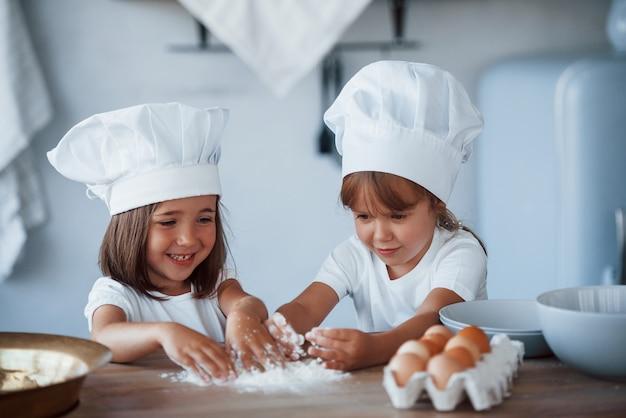 Konzentration beim kochen. familienkinder in weißer kochuniform, die essen in der küche zubereiten.