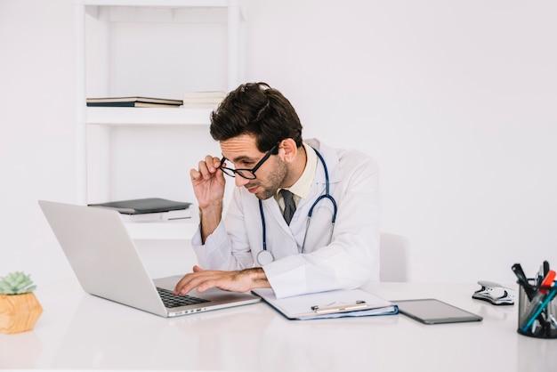 Konzentration des jungen männlichen doktors, der an laptop in der klinik arbeitet