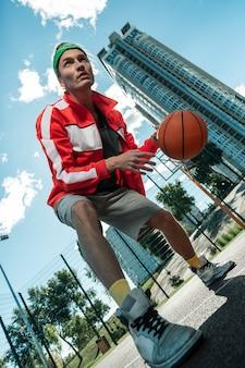 Konzentrationsfähigkeit. niedriger winkel eines ernsthaften jungen mannes, der sich auf das spiel konzentriert, während er basketball spielt