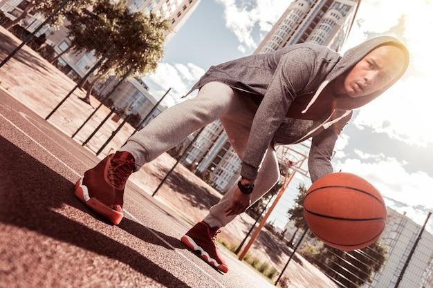 Konzentrationsfähigkeit. niedriger winkel eines ernsthaften konzentrierten mannes, der basketball spielt