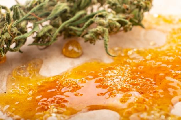 Konzentrieren sie goldenes harzwachs und trockene grüne cannabisknospen mit hohem thc in nahaufnahme