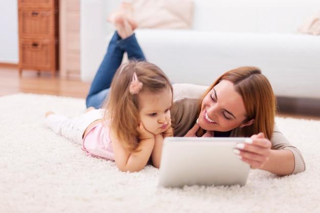 Konzentrieren sie kleines mädchen mit mutter, die digitales tablett zu hause verwendet