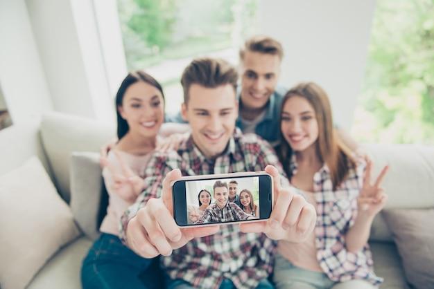 Konzentrieren sie sich auf den bildschirm des modernen telefons mit einem verschwommenen jungen menschen nehmen selfie sitzsofa