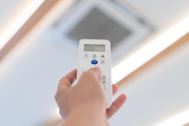 Konzentrieren sie sich auf den netzschalter der fernbedienung der klimaanlage, um sie an der decke des seminarsaals zu öffnen und auszuschalten.
