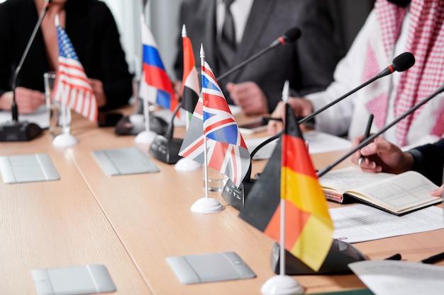 Konzentrieren sie sich auf deutsche tischfahne während des treffens, nahaufnahmefoto. abgeschnittene führungskräfte sitzen auf der pressekonferenz und treffen sich ohne krawatten