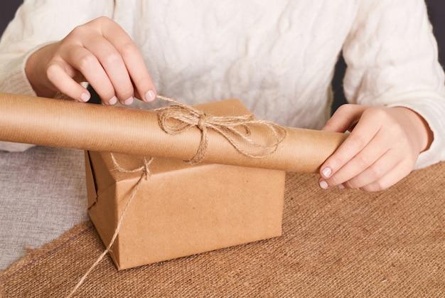 Konzentrieren sie sich auf die hände der frau in der weißen strickbox des strickpullovers. basteln sie geschenkpapier und naturgarn. schönes weihnachtsgeschenk, überraschung. geschenke für den boxtag