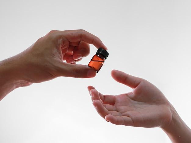 Konzentrieren sie sich auf die männliche hand, die dem patienten eine flüssige medizinflasche gibt