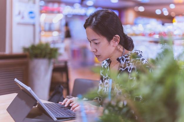 Konzentrieren sie sich auf eine frau, die im café an einem laptop arbeitet?