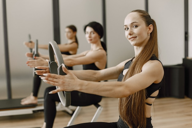 Konzentrieren sie sich auf eine frau, die in eine kamera schaut und lächelt. drei junge frauen trainieren im fitnessstudio. frauen, die schwarze sportkleidung tragen.