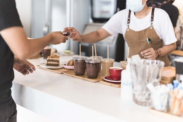 Konzentrieren sie sich auf eisgekühltes schokoladengetränk mit einer kellnerin, die digitale pager vom kunden nimmt