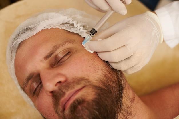 Konzentrieren sie sich auf hände in medizinischen handschuhen, die schönheitspritze für hübschen bärtigen mann im schönheitssalon anwenden. verjüngungskonzept