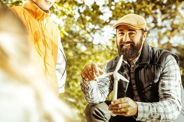 Konzentrieren sie sich darauf, dass der lehrer einem schüler an einem guten tag eine windmühle im wald zeigt