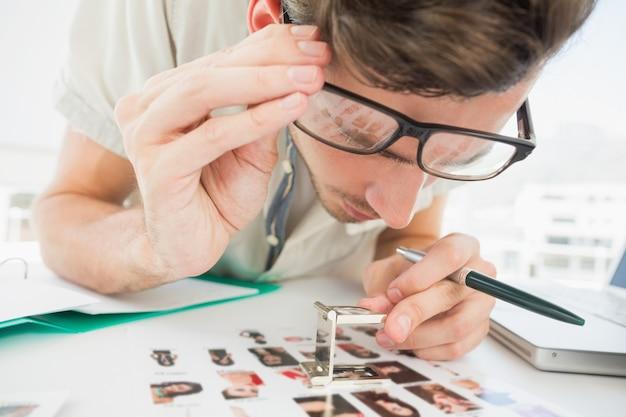 Konzentrieren sie sich den männlichen künstler, der am schreibtisch mit fotos sitzt
