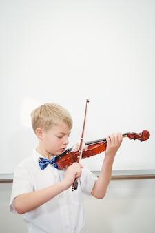 Konzentrierender student, der eine violine spielt