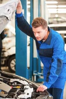 Konzentriert auf das problem. konzentrierter junger mann in uniform untersucht auto beim stehen in der werkstatt