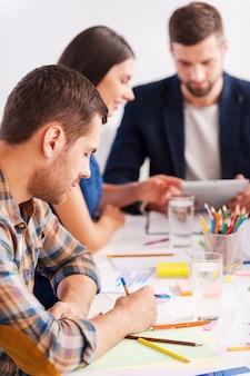 Konzentriert auf die arbeit. drei selbstbewusste geschäftsleute in smarter freizeitkleidung arbeiten zusammen am tisch