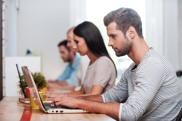 Konzentriert auf die arbeit. gruppe selbstbewusster geschäftsleute in eleganter freizeitkleidung, die an ihren laptops arbeiten, während sie an ihren arbeitsplätzen in einer reihe sitzen