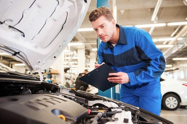 Konzentriert auf die arbeit. konzentrierter junger mann in uniform, der auto untersucht und etwas in die zwischenablage schreibt, während er in der werkstatt steht