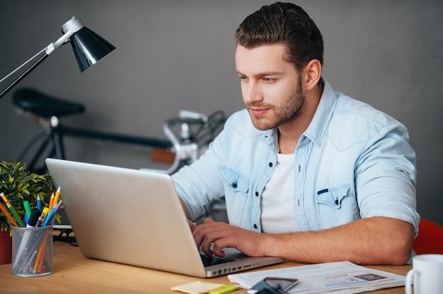 Konzentriert auf seine arbeit. selbstbewusster junger mann, der am laptop arbeitet, während er an seinem arbeitsplatz sitzt