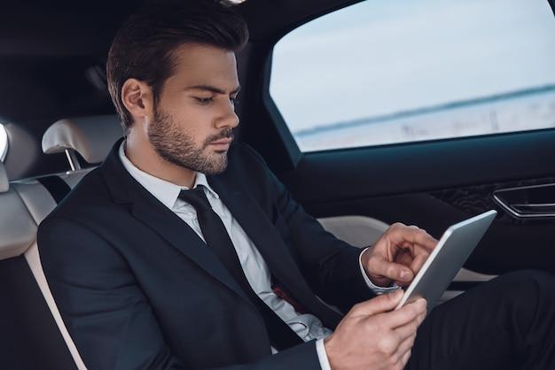 Konzentriert bei der arbeit. hübscher junger mann im vollen anzug, der mit digitalem tablet arbeitet, während er im auto sitzt
