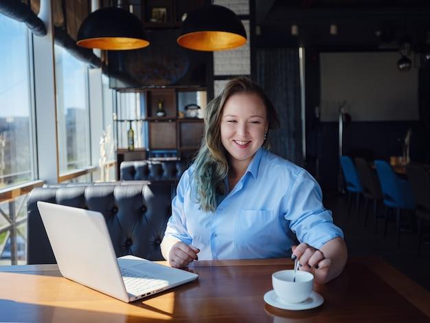 Konzentriert bei der arbeit. selbstbewusste junge frau plus größe in eleganter freizeitkleidung, die am laptop arbeitet, während sie in einem kreativen café in der nähe des fensters sitzt