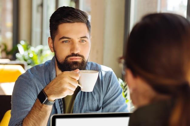 Konzentriert bleiben. ernster fokussierter mann, der seinen kollegen anschaut, während er ihm mit einer tasse kaffee gegenüber sitzt