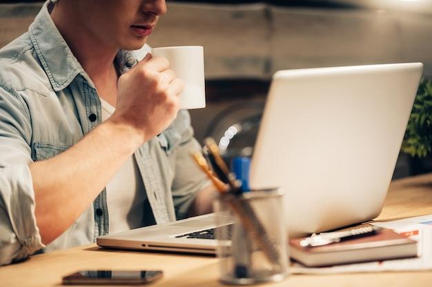 Konzentriert bleiben. nahaufnahme eines selbstbewussten jungen mannes, der spät arbeitet und kaffee trinkt, während er an seinem arbeitsplatz sitzt