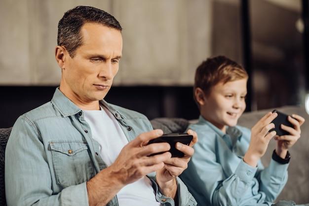 Konzentriert sich auf geräte. hübscher junger mann und sein jugendlicher sohn sitzen nebeneinander auf dem sofa und tauchen in spiele ein, jeder auf seinem gerät