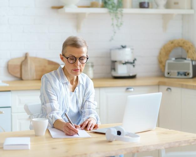 Konzentrierte ältere schriftstellerin, die etwas auf dem laptop tippt, während sie von zu hause aus online arbeitet