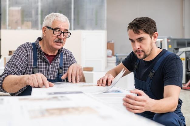 Konzentrierte ältere und junge arbeiter sitzen am seitenstapel und untersuchen gedruckte papiere
